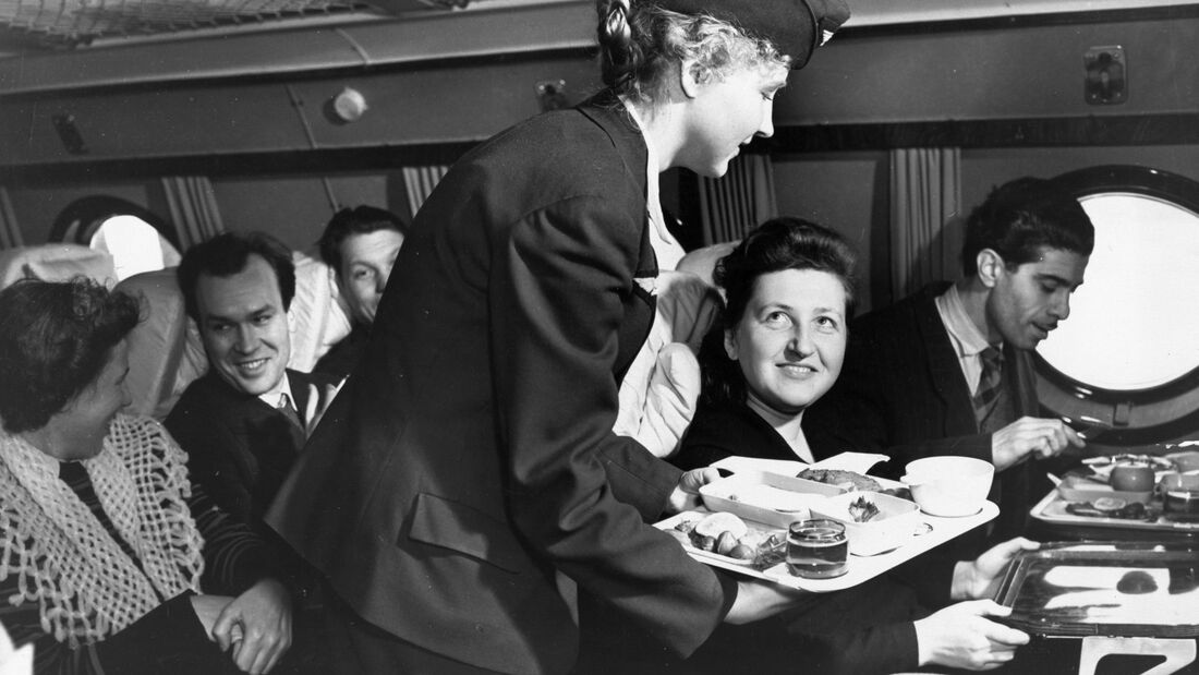 A stewardess serving a meal to passengers aboard a tu-114 airliner (at the time, the world's largest), 1959.
