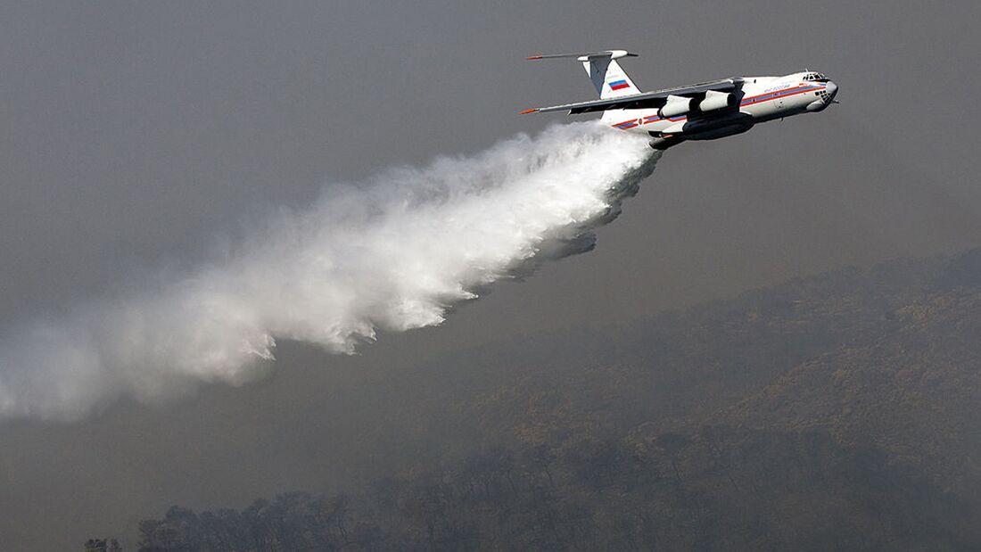 An Ilyushin-76 tanker plane sprays its l