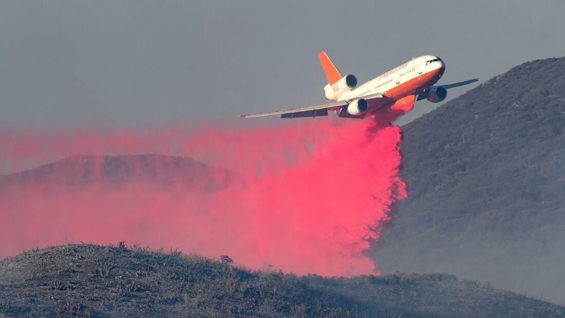 Plane dropping fire retardant on a brush fire
